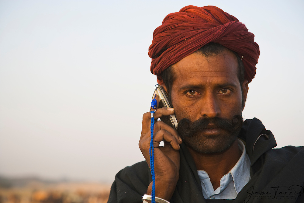 Portrait of a man with a red turban and a handlebar moustache talking on a mobile phone at the Pushkar camel fair, Rajasthan, India