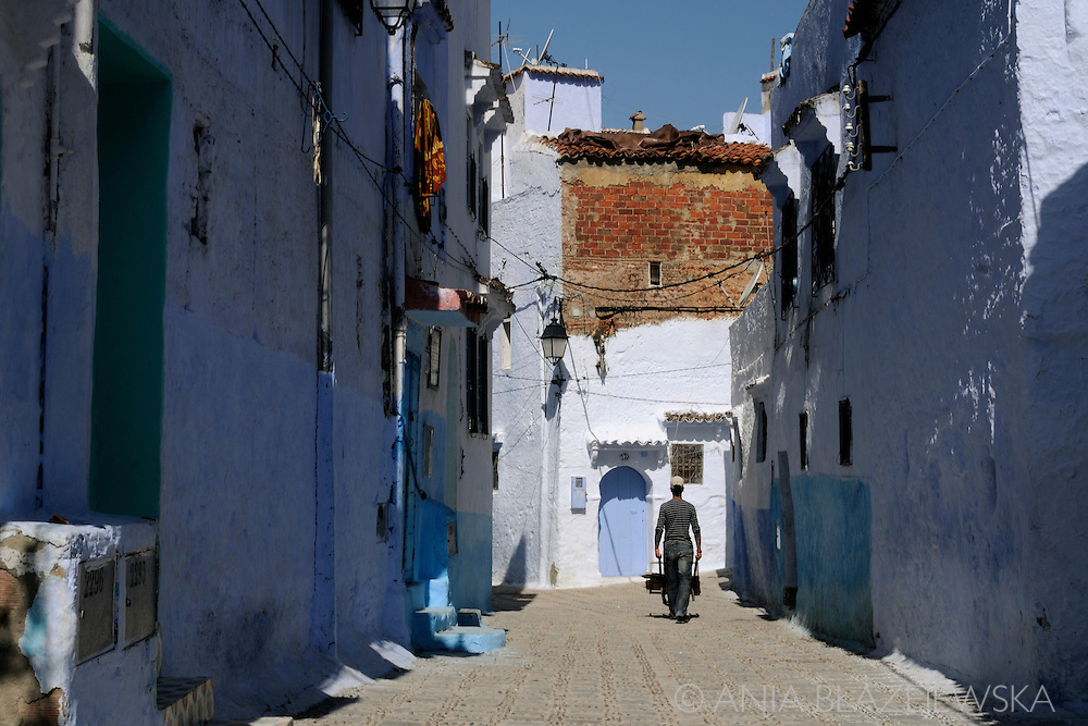 Morocco, Chefchaouen. Man with a barrow passing the Chefchaouen street.