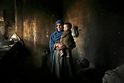 A mother holding her son stands in their refuge in an abandoned concrete building in Khushal Khan, Kabul. This building, supposedly built during the Soviet time, had been severely battered by the Civil War, and been occupied by eight internally displaced families from shomali plains. She has 11 children in one section in the building. One of the men said the government tried to demolish the building and would drive these IDP families from here.