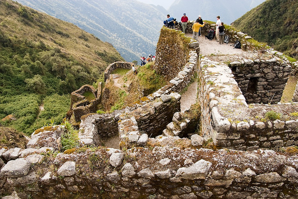 Groups of trekkers tour the Inca ruins of Phuyupatamarca along the Inca Trail to Machu Picchu, Peru.