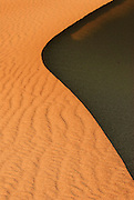The sun lights up on side of a sand dune in this image of a sand dune in Death Valley National Park.