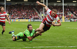 Gloucester's Jason Woodward beats the tackle of Northampton Saints Cobus Reinach to score a try during the Aviva Premiership match at the Kingsholm Stadium, Gloucester.