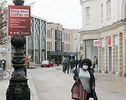 20th Feb 2021. Cheltenham, England. A woman walking through Cheltenham town centre