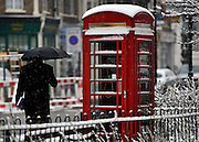 © Licensed to London News Pictures. 18/01/2013. London, A man walks past a red telephone box. Snow in West London today 18th January 2013. Photo credit : Stephen Simpson/LNP