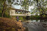 USA, Oregon, Scio, Larwood Wayside, a man walks his dog near Larwood Bridge.