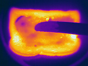 Thermogram of hot toast and butter.  The different colors represent different temperatures on the object. The lightest colors are the hottest temperatures, while the darker colors represent a cooler temperature.  Thermography uses special cameras that can detect light in the far-infrared range of the electromagnetic spectrum (900?14,000 nanometers or 0.9?14 µm) and creates an  image of the objects temperature..
