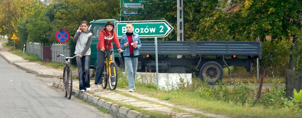 Teens with their bicycles walking along the road.  Rawa Mazowiecka  Central Poland