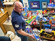 14 DECEMBER 2010 - PHOENIX, AZ: Capt Bryan Willingham (CQ) from Phoenix Fire Station 33, looks over toys at the United Phoenix Firefighters offices on Columbus in Phoenix Tuesday. Willingham's firehouse, near 24th Ave and Cactus, has adopted a family for Christmas. Donations to the United Phoenix Firefighters' toy drive are down significantly this year while demand is up. PHOTO BY JACK KURTZ