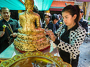 20 OCTOBER 2016 - BANGKOK, THAILAND: A woman mourning the death of Bhumibol Adulyadej, the King of Thailand, makes merit by applying gold leaf to a statue of the Buddha at Wat Phra Kaew, the most important Buddhist temple in Thailand. The King died Oct. 13, 2016. He was 88. His death came after a period of failing health. Bhumibol Adulyadej was born in Cambridge, MA, on 5 December 1927. He was the ninth monarch of Thailand from the Chakri Dynasty and is also known as Rama IX. He became King on June 9, 1946 and served as King of Thailand for 70 years, 126 days. He was, at the time of his death, the world's longest-serving head of state and the longest-reigning monarch in Thai history.       PHOTO BY JACK KURTZ