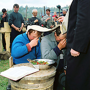 The village priest blesses the shepherds at the Measurement of the Milk Festival, Botiza, Maramures, Romania. The Measurement of the Milk festivals take place at the beginning of May, when the shepherds bring the flocks, which have spend a few days grazing in the hills, to meet the villagers at a clearing where the measurement will take place.  The sheep are milked by their owners, and the yield of each family's animals measured to determine the quota of cheese that they will receive during that season.
