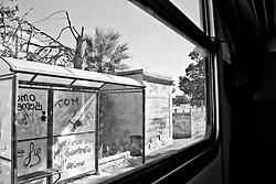 banchina coperta dove i viaggiatori attendono l'arrivo del treno. Reportage che analizza le situazioni che si incontrano durante un viaggio lungo le linee ferroviarie delle Ferrovie Sud Est nel Salento