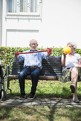 Senior man and woman exercising with resistance band and ball, Bavaria, Germany, Europe