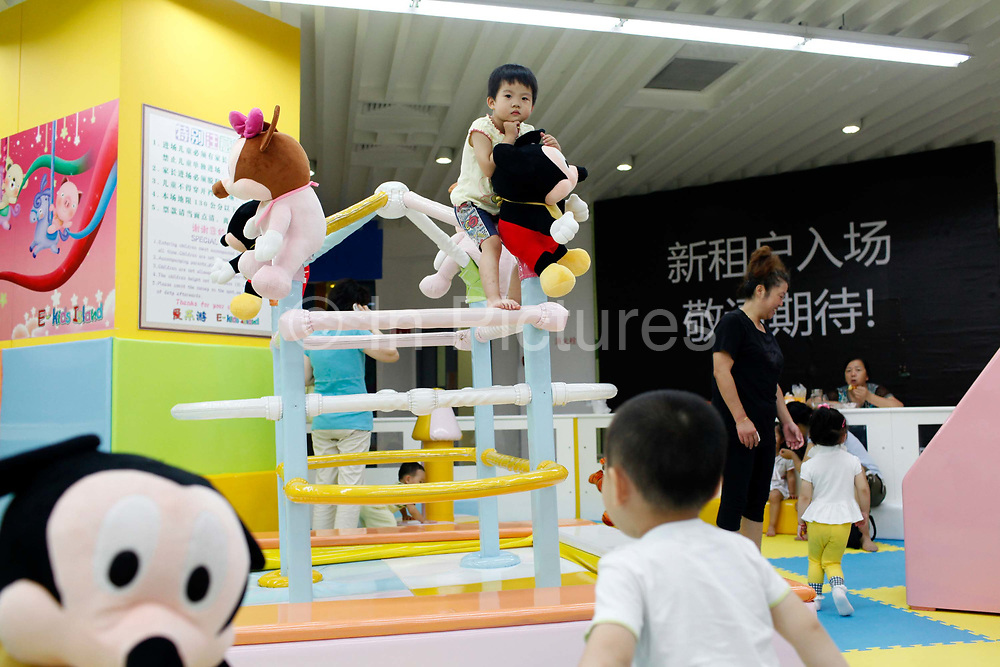 Kids play at an indoor playground in Shanghai, China on 26 July, 2011.  The director of the Population and Family Planning Commission of Guangdong, China's most populous province, has openly criticized the country's one-child policy, and said he has submitted policy change for approval to relaxation of the rules.