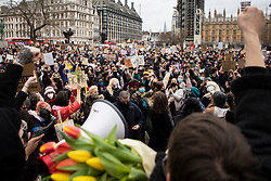 © Licensed to London News Pictures. 14/03/2021. London, UK. Protesters raise their fists in Parliament Square during a protest against the Police, Crime, Sentencing and Courts Bill 2021 that if passed will introduce new restrictions on protest. This demonstration comes after police arrested attendees at a vigil for Sarah Everard on Clapham Common last night.  Photo credit: George Cracknell Wright/LNP