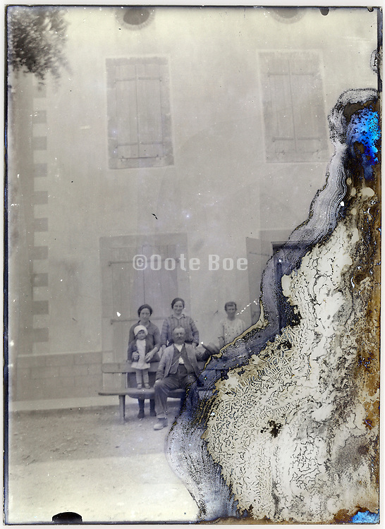 severely eroding glass plate of family posing in front of house