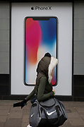 A woman walks past an ad for the new Apple iPhone X outside a branch of Carphone Warehouse, on 22nd November 2017, in London England.