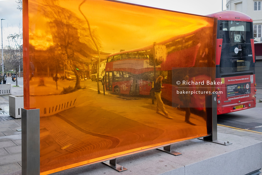 Seen through an orange-coloured prism, a figure walks along a south London street with a passing bus, their distorted perspective and geometry caused by the convex and concave shape of its thick lens, on 29th January 2021, in London, England.