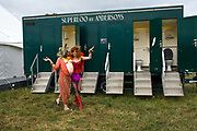 A couple in fancy dress walk past the public toilets at the Standon Calling Festival in Hertfordshire, UK<br /> Standon Calling is a small independent festival set among the hills in Herfordshire that showcases World Music, Indie Music and dance Music. It is one of the new, small and quirky boutique festivals which have become popular in the UK.