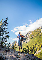 A woman hiker standing on the edge of a rocky cliff looking up at a mountain, Little Si Trail, Washington, USA.