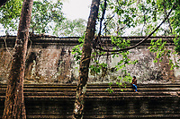 A young boy is dwarfed by a temple on the outskirts of Siem Reap in Cambodia.