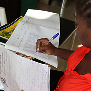 INDIVIDUAL(S) PHOTOGRAPHED: N/A. LOCATION: Onigbongbo Health Care Center, Lagos, Nigeria. CAPTION: The secretary of the Onigbongbo Health Care Center updates the register that details beneficiaries' appointments, illnesses, treatments, and other health-related matters.