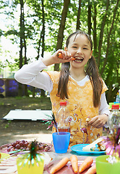 Portrait of a girl eating carrot in park, Munich, Bavaria, Germany