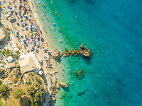 Aerial view of crowded beach with vacationers, parasols and resort, Lefkada, Greece.