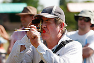 Photo by Andrew Tobin/Tobinators Ltd - 07710 761829 - Roger Hines of Cottenham who is registered blind takes aim with a special 8x20 telescopic sight during the World Peashooting Championships held at Witcham, Cambridgeshire, UK on 13th July 2013. Run in conjunction with the village fair, the Championships have been held in Witcham since 1971 when they were started by a Mr Tyson, the village schoolmaster, in order to raise funds for the village hall.Competitors come from as far afield as the USA and New Zealand to attempt to win the event. The latest technology is often used, including laser sights and titanium and carbon fibre peashooters. All peashooters must conform to strict length rules, not exceeding 12 inches, and have to hit a target 12 feet away. Shooting 5 peas at a plasticine target attached to a hay bale, the highest scorers move through the initial rounds to a knockout competition, followed by a sudden death 10-pea shootout.