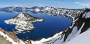 """The rim of the ancient exploded Mount Mazama volcano reflects in the deep blue lake at Crater Lake National Park, Oregon, USA. Snow covers most of Wizard Island. Published in """"Light Travel: Photography on the Go"""" book by Tom Dempsey 2009, 2010. Panorama stitched from 3 images."""