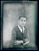 deteriorating vintage formal studio portrait of young male person, circa 1930s