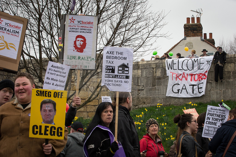 """© Licensed to London News Pictures . 08/03/2014 . York , UK . A group of protesters hang a banner that reads """" Welcome to Traitors Gate """" and a Nick Clegg effigy from York City Wall . A TUC protest march against the Liberal Democrat and Conservative coalition government passes by the Barbican Centre in York . The second day of the Liberal Democrat Spring Conference today (Saturday 8th March 2014) . Photo credit : Joel Goodman/LNP"""