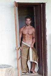 good looking man standing in a doorway wearing a blanket