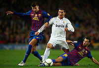 BARCELONA, SPAIN - JANUARY 25: Gerard Pique and Sergio Busquets of Barcelona competes for the ball with Cristiano Ronaldo of Real Madrid during the Copa del Rey quarter final match between Barcelona and Real Madrid at Estadio Nou Camp on January 25, 2012 in Barcelona, Spain.. (Photo by Manuel Queimadelos)