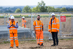 HS2 workers monitor anti-HS2 activists after some had occupied mature oak trees and a trailer transporting wood chip in order to try to prevent or delay tree felling alongside the Fosse Way in connection with the HS2 high-speed rail link on 24th August 2020 in Offchurch, United Kingdom. The controversial HS2 infrastructure project is currently expected to cost £106bn and will destroy or significantly impact many irreplaceable natural habitats, including 108 ancient woodlands.