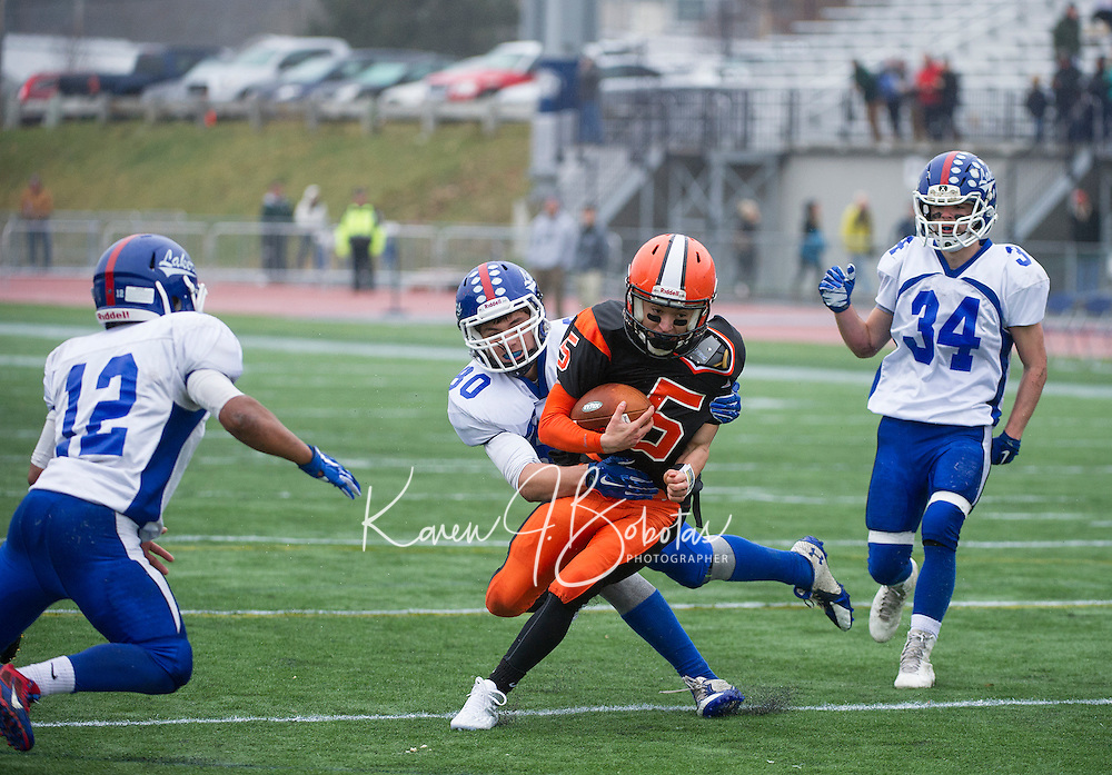 Interlakes Zach Swanson wraps up Newport's quarterback Dylan Mcnamara during NHIAA Division III state championship football held at UNH on Sunday.  (Karen Bobotas/for the Laconia Daily Sun)