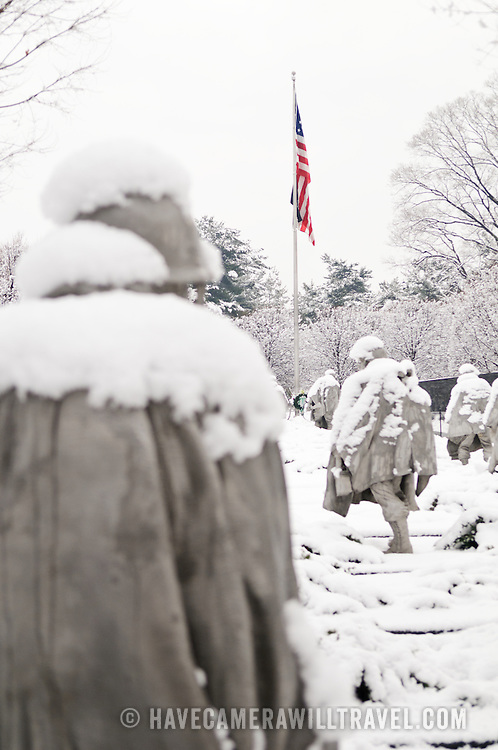 """The Korean War Memorial on the National Mall covered in a fresh blanket of snow. The bottom left corner of the frame is the back of one of the statues of soliders. The Korean War Veterans Memorial, unveiled in 1992, sits on the northwestern end of the National Mall, not far from the Lincoln Memorial. It consists of several elements designed by different people and groups. It has a triangular footprint with the main elements being """"The Column"""" consisting of 19 stainless steel solders, each over 7 feet tall, and a reflective granite wall etched with the faces of thousands of Americans who lost their lives in the war. At one end of the triangle, behind the soldiers, is a grove of trees. At the other is a large American flag and a small Pool of Remembrance. Among the designers were Frank Gaylord (the soldiers) and Louis Nelson (the reflecting granite wall)."""
