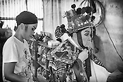 An actress assists the God of fortune backstage at the Chinese opera. The dressing room is a simple tent with makeshift preparation areas. The I-Hsin opera troupe are preparing for a performance.