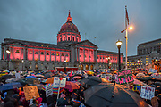 """San Francisco City Hall's pink lights surprise the crowd, turning on just as the they begin to march from the rally at Civic Center Plaza. Signs among the crowd read, """"Black trans + undocumented lives matter,"""" """"Not my president,"""" """"Build bridges not walls,"""" Untrump the world,"""" and """"Dissent is patriotic."""""""