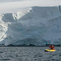 A kayaker paddles near a calving glacier on Wiencke Island, near the Antarctic Peninsula, Antarctica.
