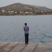 Syrian refugee Ayman Al Abood, 29, fishing in the port of Lakki.