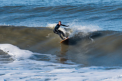 © Licensed to London News Pictures. 25/02/2019. Aberystwyth, UK. A surfer takes advantage of a big Atlantic swell, combined with the high tide, bring huge waves rolling in to the harbour lighthouse  in Aberystwyth on a sunny and warm February morning.. Photo credit: Keith Morris/LNP
