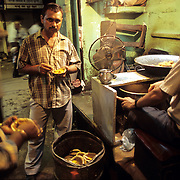 A vendor selling spicy kachoris in the alleys of old Delhi. The kachori (kachod'i) has many avatars, but is basically a flavored crispy wheat puff, stuffed with potato, peas and lentils. It is sold in leaf plates accompanied by a dry chickpea preparation called ghugnil, or with a spicy potato curry.