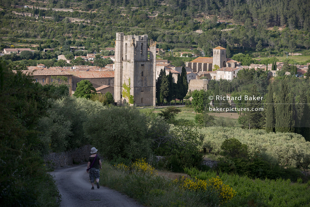 A walker descends a country path towards the pre-Romanesque tower of the Abbey of Sante-Marie D'Orbieu and the church of Saint-Michel, on 21st May 2017, in Lagrasse, Languedoc-Rousillon, south of France. Lagrasse is listed as one of France's most beautiful villages and lies on the famous Route 20 wine route in the Basses-Corbieres region dating to the 13th century.