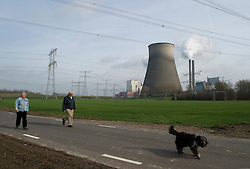 Residents of Geertruidenberg, NL, walk their dog next to the Essent Energie power station, on Monday March 22, 2010, in Geertruidenberg, Netherlands. Essent Energie is owned by RWE AG. (Photo © Jock Fistick)