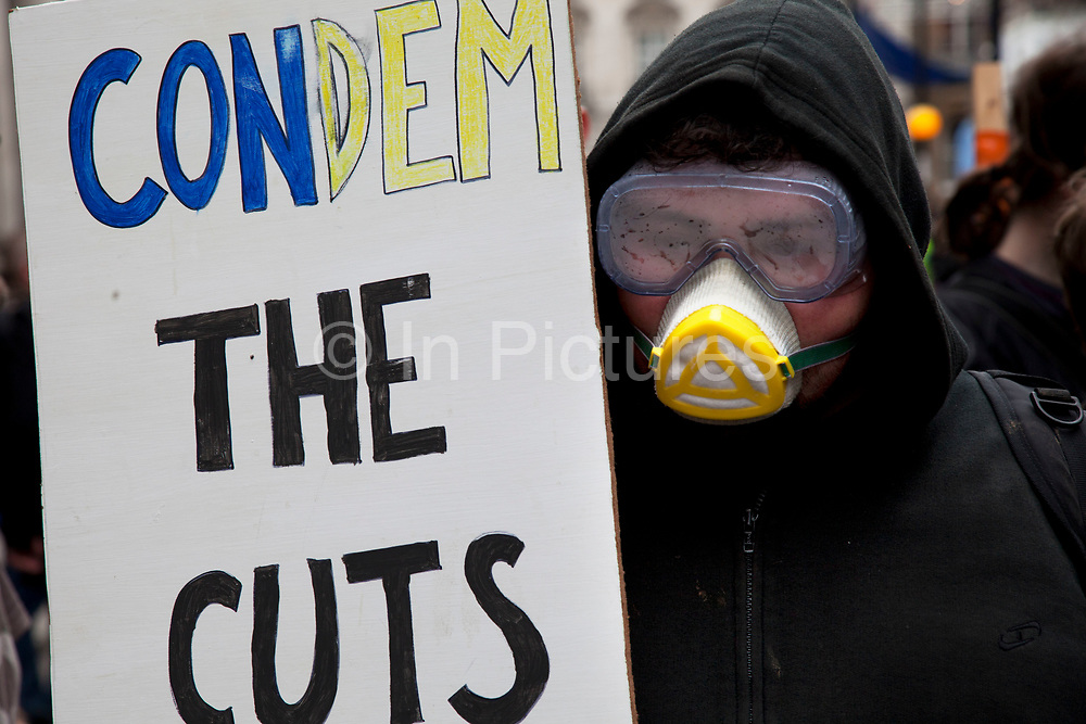 Occupy LSX member in support of the police with placards and wearing steamed up goggles and face mask. On a day when 400,000 public sector workers go on strike over cuts, pay and pensions, approximately 30,000 off duty police officers, marched in the capital against projected job losses over the next four years. London, UK.