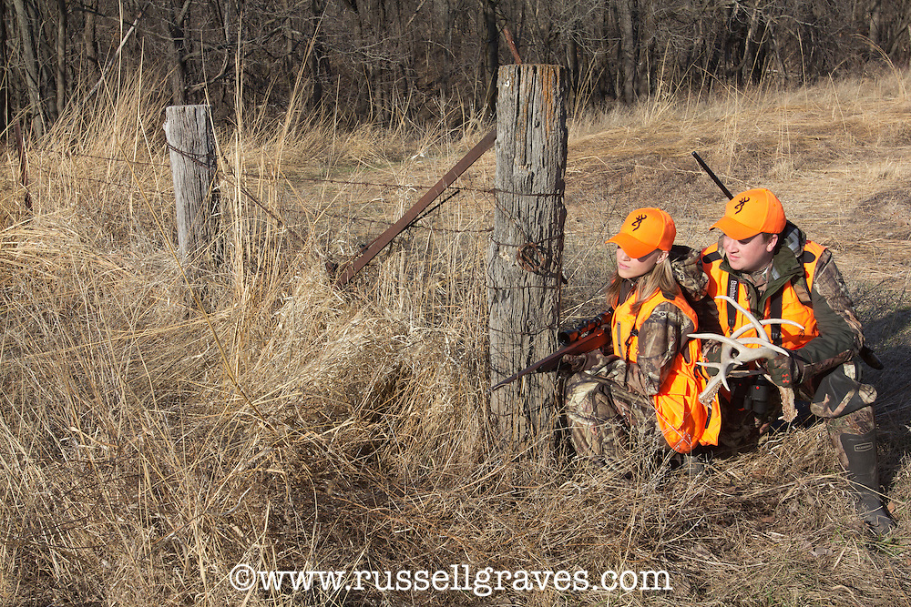 MALE AND FEMALE HUNTERS WEARING BLAZE ORANGE WHILE RATTLING FOR DEER