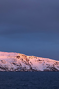 Scenic winter landscape of snow-capped mountain against moody sky at sunrise, Havoysund, Norway