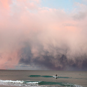 11.18.08 - Isolated snow flurries off the coast of Wrightsville Beach North Carolina form an amazing display for a lone paddle boarder beneath them.