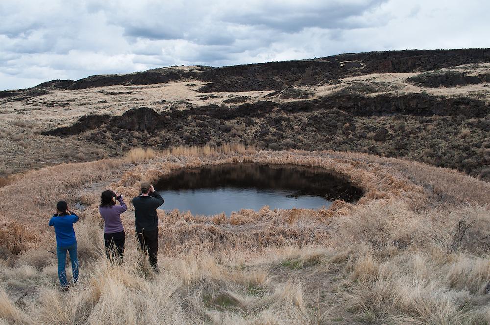 People exploring Malheur Maar at Diamond Craters Outstanding Natural Area, Oregon.