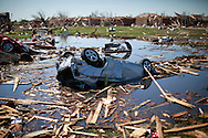 A tornado destroyed car lies upside down in the pond next to Briarwood elementary school in Oklahoma City, Oklahoma May 22, 2013.  Rescue workers with sniffer dogs picked through the ruins on Wednesday to ensure no survivors remained buried after a deadly tornado left thousands homeless and trying to salvage what was left of their belongings. Curvature of horizon in the photo is due to an ultra-wide angle lens.  REUTERS/Rick Wilking (UNITED STATES)